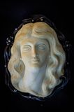Cameo with the girl's face from the Tusk of a mammoth. Royalty Free Stock Photos