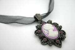 Cameo Necklace. Purple cameo necklace on white royalty free stock photo