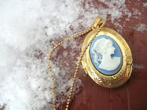 Cameo Necklace in the Snow. A cameo locket with snow surrounding it royalty free stock images