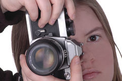 Camera 3. A woman positions a camera for a vertical shot. Half of the woman's face is visible stock photo