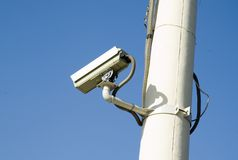 Camera. A security camera peers   on the pole  with bule sky Royalty Free Stock Photo