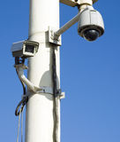 Camera. A security camera peers   on the pole  with bule sky Stock Photo