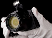 The camera against a dark background holding gloves. Hold the camera in white gloves Royalty Free Stock Image