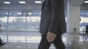 Passengers in the airport hall. The camera is in the airport hall. Businessman with silver suitcase walks on the foreground. Young man with backpack walks on the stock video