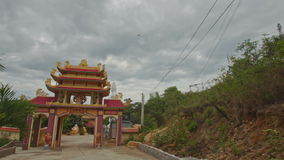 Camera Approaches Buddhist Temple Gates against Cloudy Sky stock video