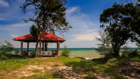 Camera Approaches Pavilion on Beach of Azure Sea. Camera approaches red roof pavilion among tropical plants on beach against azure sea sky and fleecy clouds stock video footage