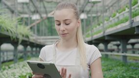 Camera approaches to charming blond woman using tablet in greenhouse. Beautiful young Caucasian agronomist or biologist