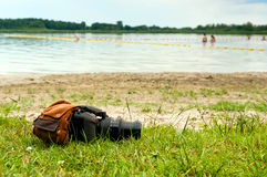 Camera and backpack on lake shore Stock Photos