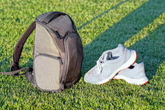 Camera backpack and shoes on grass. Stock Photography