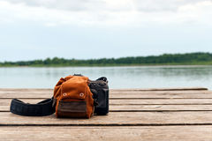 Camera and backpack on wooden dock Royalty Free Stock Images