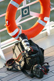 Camera bag. On the cruise ship deck floor next to a fence with life jacket Royalty Free Stock Image