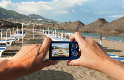 Camera on Beach. Taking a photo on a beach with a compact camera Royalty Free Stock Photo