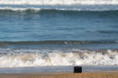 Camera on beach taking timelapse of rolling waves. Focus on camera taking video or timelapse footage from sandy beach towards rolling surf and waves royalty free stock photos