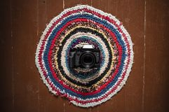 The camera is on a beautiful home round patterned carpet, lying. On the brown floor at the entrance. Close-up royalty free stock image