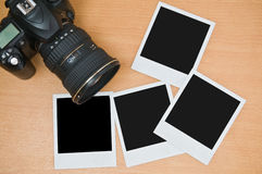 Camera with blank polaroid frames. On wooden background Royalty Free Stock Photos
