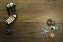 Camera boat and compass decorate on wooden table with starfish world glass marble and turtle. In Thailand Stock Photos