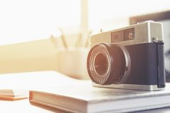 Camera,book and pens on a wooden table. In front of the window stock images