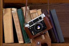 Camera and books. Vintage camera and old books on a shelf Royalty Free Stock Photo