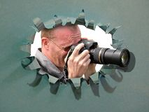 Camera cameraman using lens through hole in card breakthrough tear disguise. Concept photo of a cameraman using zoom lens through punch hole in card royalty free stock images