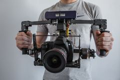 Camera carbon gimbal with dslr camera with man hands. Selfmade technology Royalty Free Stock Photo