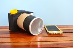 Camera and phone made of cardboard. Camera and cellphone made of cardboard on a wooden floor Stock Photo