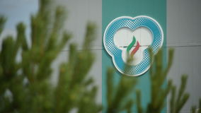 Camera Changes Focus from Logo Sign to Green Pine Branches. KAZAN, TATARSTAN/RUSSIA - JUNE 08 2015: Camera changes focus from logo on production plant wall to stock footage