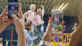 Camera Changes Focus from Phones in Hands to Joyful Girls. Camera changes focus from phones in mothers hands to joyful girls jumping in shopping mall stock video
