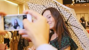 Camera Changes Focus from Smartphone to Posing Nice Girl. Camera changes focus from smartphone in man hands to beautiful girl posing with umbrella in fashion stock footage