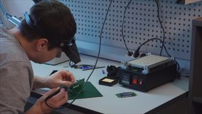 Camera charge repair. Technician examining broken part printed circuit with tweezers. Removes damaged components using a blowtorch stock video footage