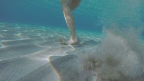 Young Woman Beeing Chased Underwater. Camera Is Chasing Underwater A Female Running Away On A Sandy Tropical Seabed stock footage