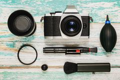 Camera with cleaning kit, flat lay. Vintage style camera and lens with cleaning kit - air pump, cleaning pen, brush and lens protective filter on rough painted Stock Image