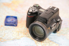 Camera and compass on map Stock Images
