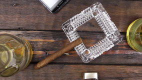 Camera crane, top view, modern wooden desk, glass of whiskey and cigar .