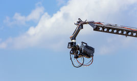 Camera on a crane. A TV camera on a crane during a sport event, sky background Royalty Free Stock Image