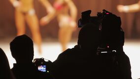 Camera crew shooting video of bodybuilding contest, interesting occupation