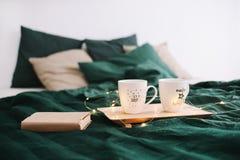 Camera da letto accogliente con le tazze da caffè ed il libro a letto Di natale vita ancora Concetto di feste, di Natale e del nu immagine stock