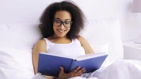 Camera da letto africana del libro di lettura della donna a letto a casa stock footage