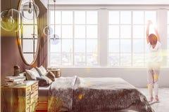 Camera da letto bianca e grigia, vista laterale, donna fotografia stock