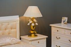 Camera da letto bianca reale di lusso nello stile antico Comodino con una lampada elegante Immagini Stock