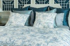 Camera da letto con i cuscini blu sul letto Immagini Stock