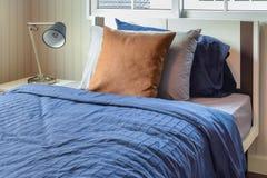 Camera da letto con i cuscini marroni sul letto blu Fotografia Stock Libera da Diritti