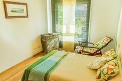 Camera da letto con il letto, il cassettone, la sedia di oscillazione e la finestra fotografia stock