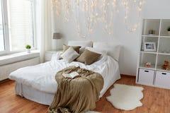 Camera da letto con il letto e la ghirlanda di natale a casa Immagine Stock