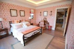 Camera da letto con la carta da parati rossa del fiore fotografia stock