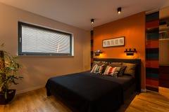 Camera da letto del progettista con la parete arancio Fotografia Stock Libera da Diritti
