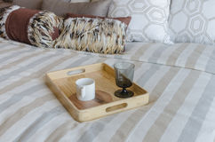 Camera da letto di lusso con la tazza ed il vetro sul vassoio di legno Fotografia Stock