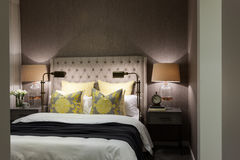 Camera da letto di lusso illuminata alla notte con il primo piano delle lampade da tavolo Fotografia Stock