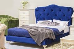 Camera da letto di lusso nello stile antico con il letto blu del velluto ed il comodino bianco immagine stock