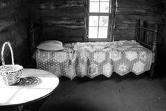Camera da letto di vecchia cabina di ceppo pionieristica fotografia stock
