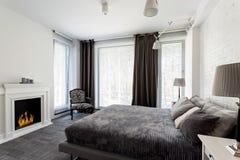 Camera da letto grigia con il camino ed il letto fotografia stock